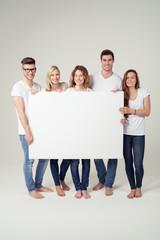 moderne junge leute zeigen ein weißes plakat