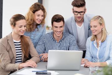junge leute im büro schauen gemeinsam auf laptop