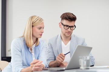 zwei kollegen schauen sich etwas am laptop an