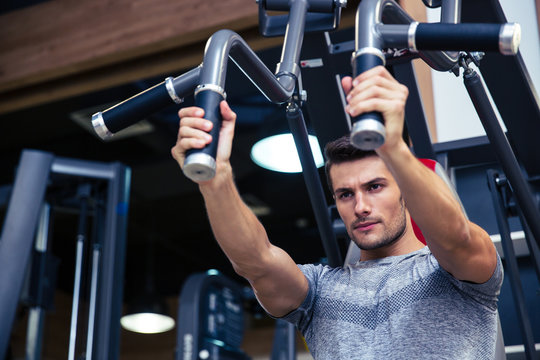 Bodybuilder doing exercise on fitness machine in gym