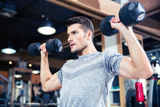 Man workout with dumbbells at gym