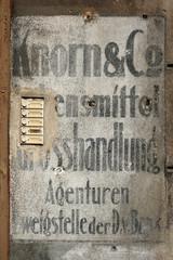 Hauseingang mit altem Klingelschild und Werbung