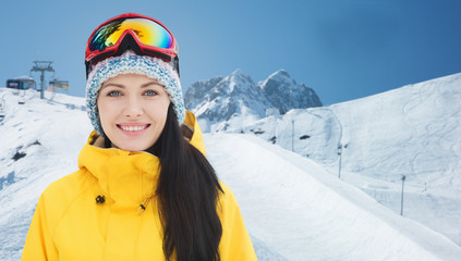 happy young woman in ski goggles over mountains
