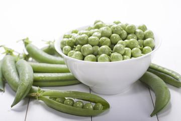 Fresh green peas in a white bowl  .