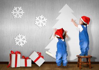 Funny Little twins dressed Santa hat, glue Christmas tree on wal