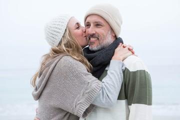 Cute woman giving a man a kiss