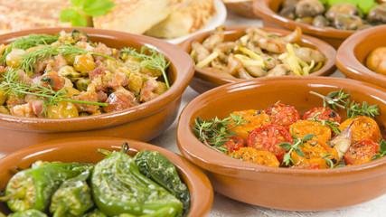 Spanish Tapas  - Tomates al Ajillo (Tomatoes with garlic), Pollo al limon con ajo (chicken with garlic) and Padron Peppers.