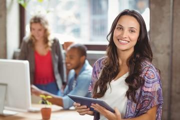 Portrait of smiling businesswoman holding digital tablet