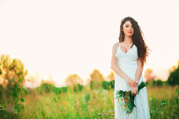 beautiful young woman in a field with a bouquet in hands