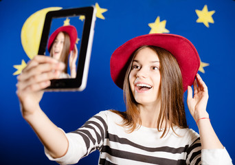 Young happy woman trying on red hat and making selfie