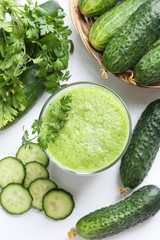 Glass of fresh cucumber juice on white wooden table