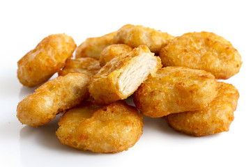 Pile of golden deep-fried battered chicken nuggets isolated on w