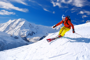 Poster Winter sports Skier skiing downhill in high mountains against blue sky