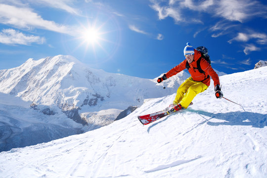 Skier skiing downhill in high mountains against blue sky