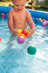 Child plays with balls in the pool
