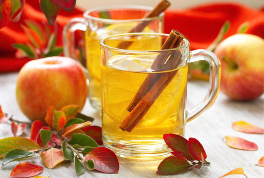 Hot drink with apple juice, lemon and cinnamon in autumn