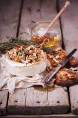 Baked Camembert with honey, walnuts and timanian on an old cutting board.