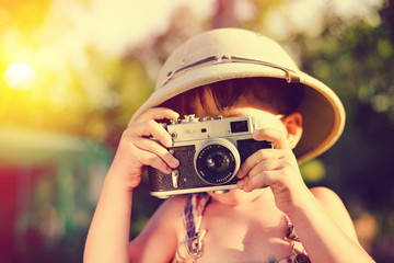 Little boy wearing pith helmet making photo with vintage camera