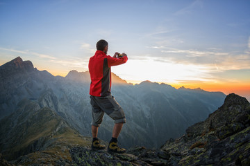 Trekker photographing the sunset with his smartphone