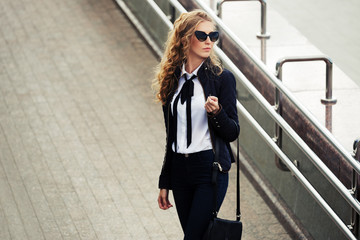 Young fashion business woman in sunglasses on the city street