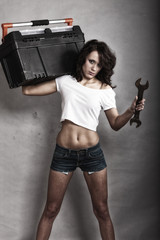 Sexy girl holding toolbox and wrench spanner