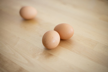 Raw eggs on wooden table