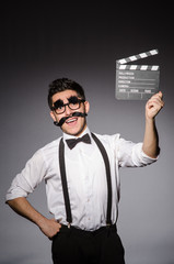 Young caucasian man with false moustache and clapperboard agains