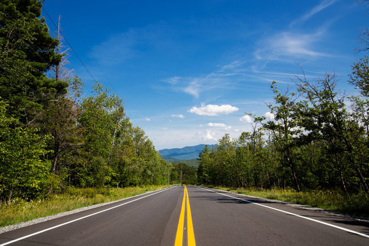 Winding road in Adirondack mountains, upstate New York, USA. Transportation, travel, explore, vacation, summer, destination, driving and nature concept