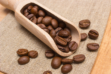 Heap of coffee beans with wooden scoop on jute canvas on table