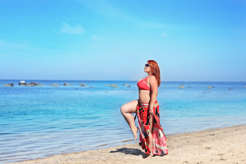 Plus size redhead woman in sunglasses resting on beach