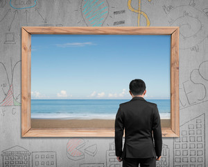 Businessman looking at wooden frame window with sea beach