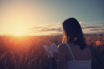 Young handsome girl reading book outdoors in sunset in the field