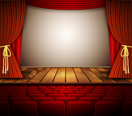 A theater stage with a red curtain, seats.