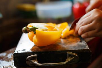 female's hand cutting big chilli peper