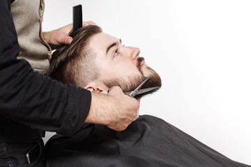 Barber cutting a beard of young brutal man in studio