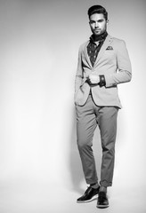 attractive fashion male model dressed elegant - casual posing against wall