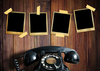 Old picture and old telephone on wood background.