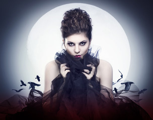 Lovely young female vampire in the night moon.
