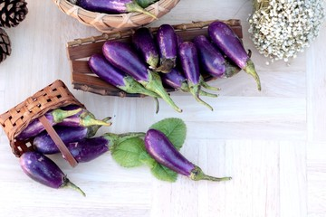 Purple eggplants fresh for cooking on wood background.