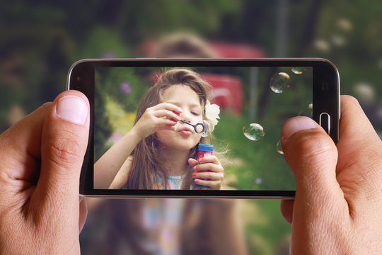 Male hand taking photo of Vintage Portrait of beautiful girl blowing bubbles with cell, mobile phone. Kids, childhood, family concept.
