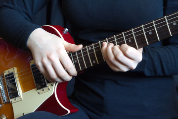 Musician in black on red six strings electric guitar playing. Hands of the musician closeup