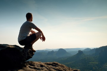Young man in black sports pants and grey shirt  is sitting on cliff's edge and looking to misty valley bellow Fotomurales