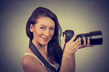 Professional female photographer holding digital camera and smiling.
