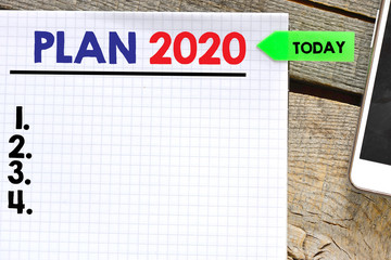 Plan 2020  on paper sheet with mobile phone  on wooden background