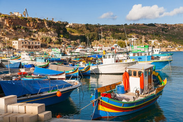 Port of Mgarr on the small island of Gozo, Malta. Traditional maltese colorful painted fishing boat.