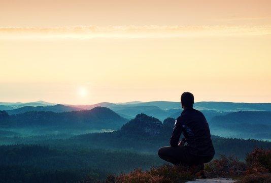 Sunrise sports. Hiker in in dark sportwear in  squatting position on a rock in heather bushes, enjoy the scenery