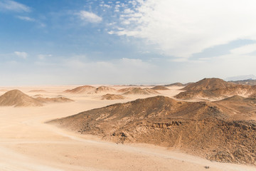 Beautiful desert landscape of Egypt. Yellow sand, mountains, clouds and blue sky.