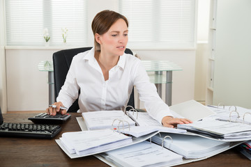 Businesswoman Calculating Financial Data At Desk