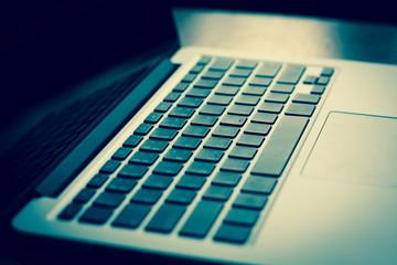 open laptop with black screen on modern wooden desk