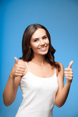 young woman showing thumb up gesture, on blue